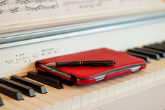 The book on the piano. Electronic book in the red cover on piano Stock Photography