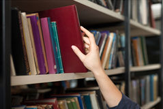 A book picked or taken with a hand from a book shelf in the libr Royalty Free Stock Image