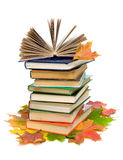 Book on a pile of books and maple leaves. Open book on a pile of books and autumn maple leaves closeup on white background Stock Photos