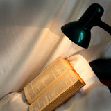 Book on pillow lit reading lamp Stock Image