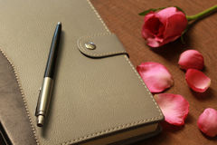 The book with pink rose and pen Royalty Free Stock Photo