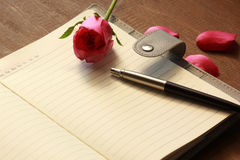 The book with pink rose and pen Stock Images