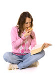 Book and pizza. Young woman reading the book and eating pizza Stock Image