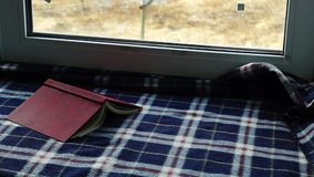 Book and plaid and snow outside the window stock footage