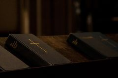 Book of Prayer. A closed black book with a yellow cross on it, being the Book of Common Prayer stock photo