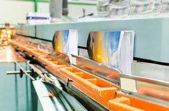 Book production perfect bound line in offset print plant. Brochure and magazine stitching process. Close-up of the offset conveying process of a full-automatic Stock Photo