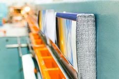 Book production perfect bound line in offset print plant close up. Book, magazine, catalog production line into press plant house. Binding cover and assembling Royalty Free Stock Images