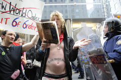 Book reading. TORONTO-JUNE 26: A protester reads out lines from a Stephen Hawking book titled  A brief history of time  to the riot police officers during the Stock Image