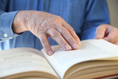 Book reading. A senior man's hands on a book Stock Photography
