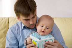 Book reading. Young father reads his one year old son a book royalty free stock photos