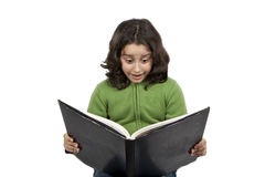 Book reading girl. A pretty girl is reading a big black book and shows her surprised face Royalty Free Stock Images
