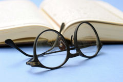 Book and reading glasses stock photography
