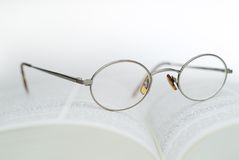 Book and reading glasses. High key closeup of reading glasses on an open book royalty free stock photography