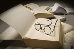 Book reading. Pair of reading glasses on top of an open book, near other open books Stock Images