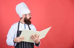 Book recipes. According to recipe. Man bearded chef cooking food. Culinary arts concept. Amateur cook read book recipes. Man learn recipe. Try something new royalty free stock photo