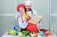 Book recipes. Helpful culinary book. Woman chef and man cooking food together. Culinary family concept. Couple in love royalty free stock photo