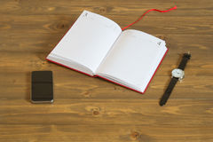 The book for records and hours with the phone on the table. Notepad phone and clock on the table Stock Images