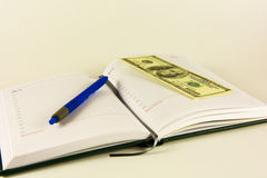 Book for records, pen and banknotes 100 dollars Royalty Free Stock Photography