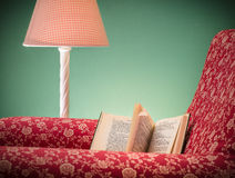 Book and red armchair. Opened book on red armchair rest left after reading, with green background and pink lamp, One page folded down (dog ears) to mark current Royalty Free Stock Photo