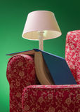 Book and red armchair. Book on red armchair rest left after reading, with green background and pink lamp illuminating the scene Stock Photo