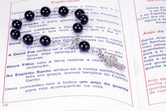 A book and rosary beads. The book of Catholic Church liturgy and rosary beads Stock Photo
