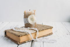 The book is in rustic style on a white table. With a candle and a pearl necklace Royalty Free Stock Image