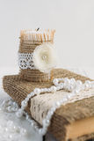 The book is in rustic style on a white table. With a candle and a pearl necklace Stock Photography
