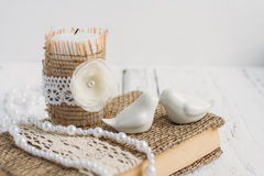 The book is in rustic style on a white table. With a candle and a pearl necklace Stock Photo