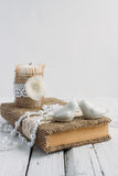The book is in rustic style on a white table. With a candle and a pearl necklace Stock Image