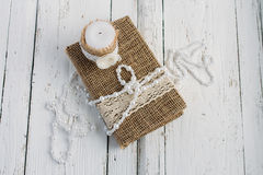 The book is in rustic style on a white table. With a candle and a pearl necklace Stock Images