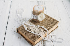 The book is in rustic style on a white table. With a candle and a pearl necklace Royalty Free Stock Photos