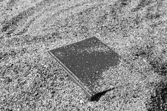 Book on the sand on a blurred background, covered with sand, black and white, monochrome. Royalty Free Stock Image