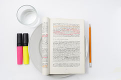 A book served as a meal. A student book, in italian language, served as a meal on a white plate, with highlighters, a pencil and a glass of pure still water. The Stock Photography