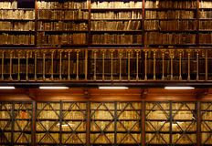 Book shelves in library. Many old books are standing on wooden shelves in two-tier library , with handrail on foreground Royalty Free Stock Photos