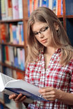 Book shop owner. Small business owner in the store. Portrait of young female salesperson in book shop reading book. Beautiful blond Caucasian woman in eyeglasses royalty free stock photo