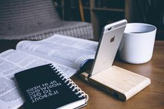 Book and Silver Iphone 6 on Top of Table Stock Photography