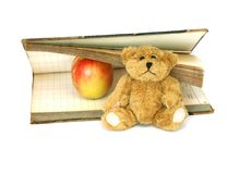 Book, small bear and apple isolated on white Stock Images