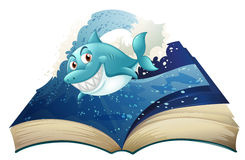 A book with a smiling blue shark and waves Stock Photo