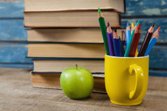 Book stack, color pencils and apple on wooden table Stock Photography