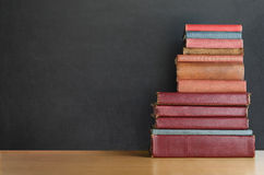 Book Stack on Desk with Chalkboard Background Stock Photos