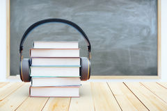 Book stack with headphones. On chalkboard background. 3D Rendering. Audio books concept Royalty Free Stock Photography