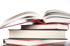 Book stack with open book. Open book sitting on a stack of books on desk, isolated Royalty Free Stock Image