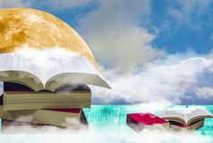 Book stack, placed on a wooden balcony, has a blue sky and large moon background. royalty free stock image