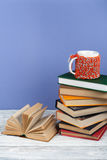 Book stacking. Open book, hardback books on wooden table and blue background. Back to school. Copy space for text. Stock Image