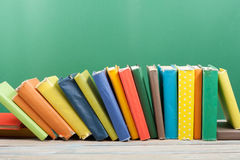 Book stacking. Open hardback books on wooden table and green background. Back to school. Copy space for ad text.  Royalty Free Stock Photo