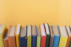 Book stacking. Open hardback books on wooden table and yellow background. Back to school. Copy space for ad text.  stock photos