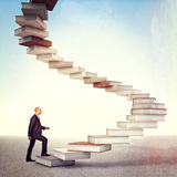 Book stair and man. Young businessman go up on 3d books stair Stock Photography