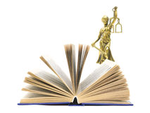 Book and the statue of justice. Open book and the statue of justice isolated on white close-up royalty free stock image