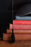 Book Steps Leading to Graduation Cap. A pile of old, used vintage books, arranged as steps leading up to a graduation cap at the top (mortarboard Royalty Free Stock Images
