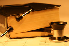 Book and stethoscope. On a EKG printout Stock Image